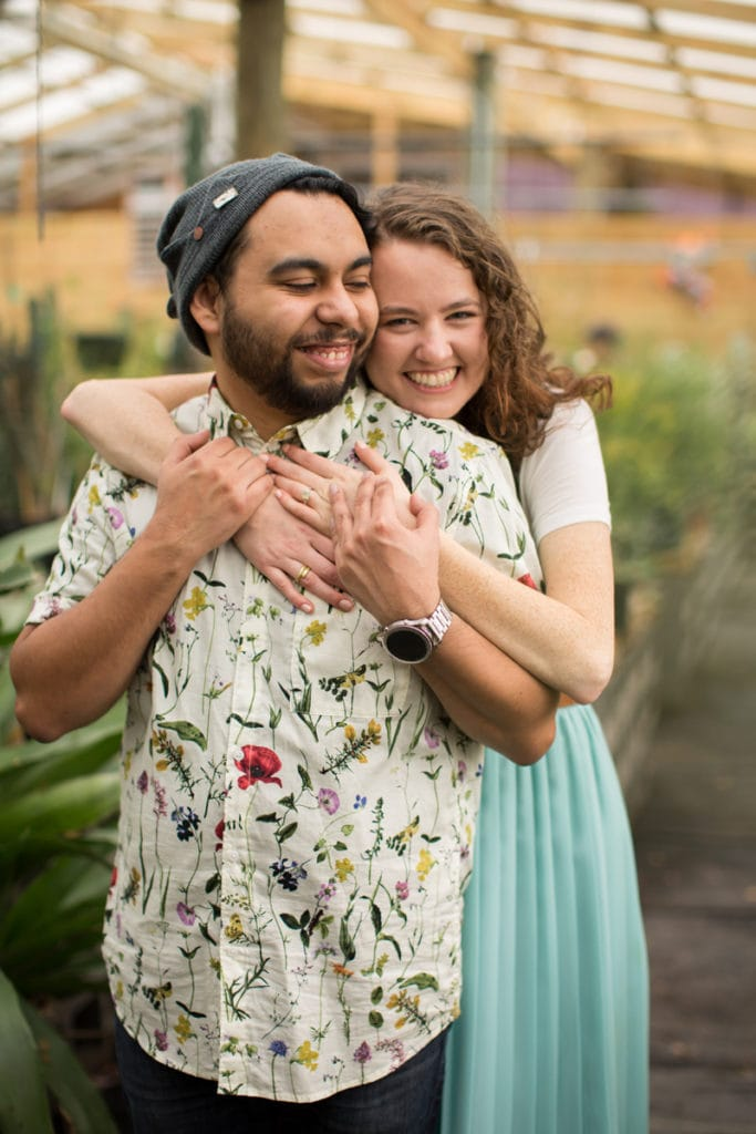 Family Photography - a young couple embrace each other smiling in a large greenhouse