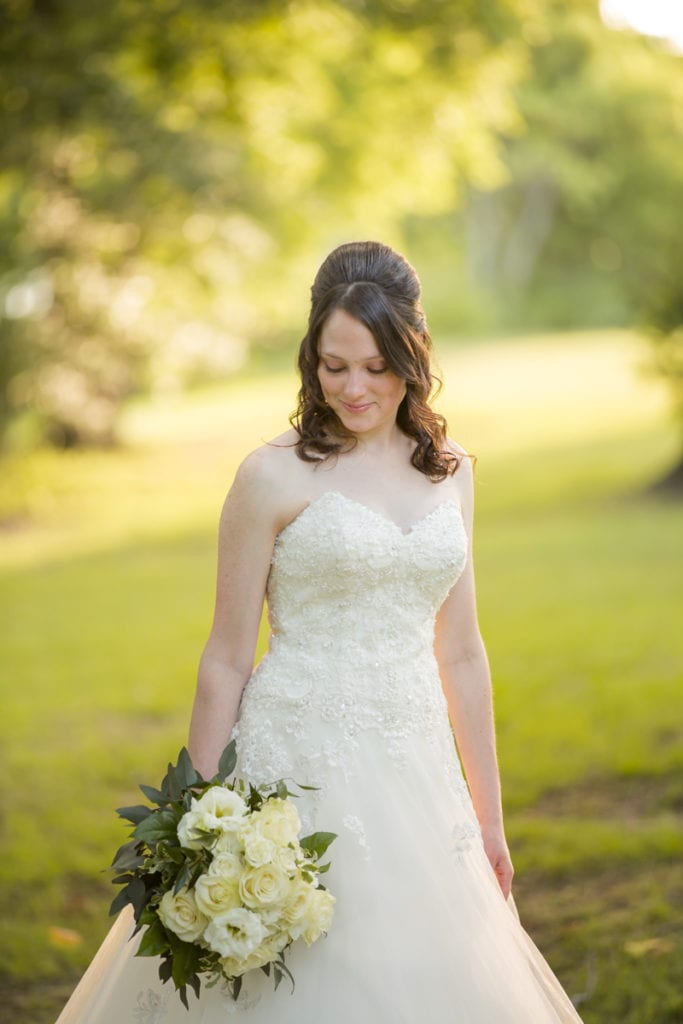 Wedding Photography - a young bride holds bouquet of flowers happy outdoors