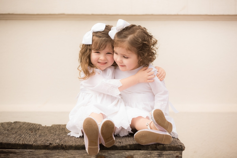 Family Photography - two young sisters hug, they're both wearing white dresses and bows