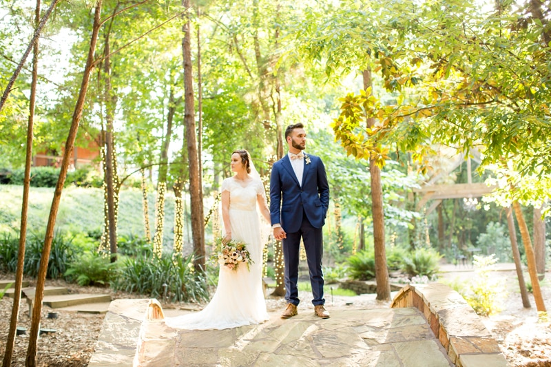 Wedding Photography - Bride and groom stand in forest hand in hand, the light shines from behind